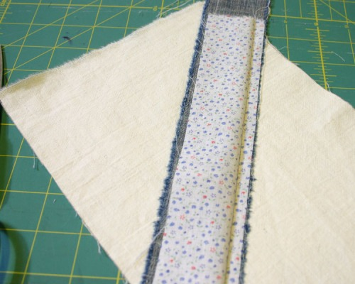 With the right sides together, line the next strip up with the first, stitch and press open.  Repeat this process on both sides of the starting strip until the rectangle is covered.