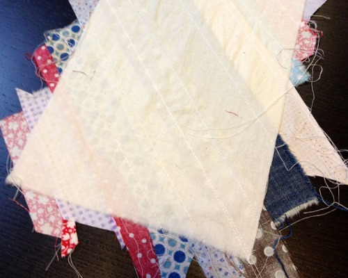 Once you have covered the unbleached muslin with strips, press once more and flip it over to trim the excess pieces.