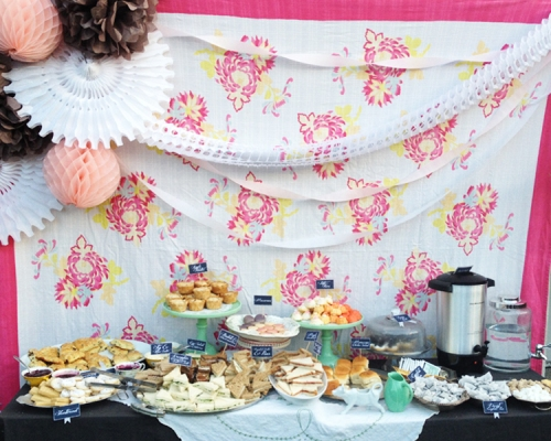 The Copy: Clustered tissue fans and streamers create a lovely backdrop for this tea party shower.