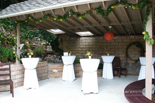 With appetizers and drinks in hand, guests went up to the ceremony location to eat and talk at tall cocktail tables. The awning was draped with a garland that I wired together from tree branches (free!), rosemary and protea.