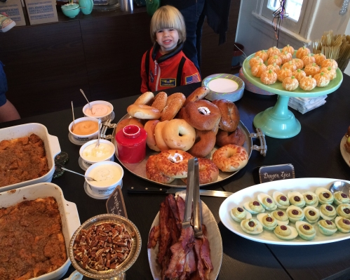 A tiny astronaut checks out the buffet of bagels, pumpkin french toast casserole, and bacon.