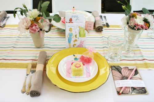 I have 6 yellow plates and 6 speckled plates, so I rented 12 small white bread plates to tie mine together. Each place setting had a cheeky favor bag, a birthday card for the baby, a baggie of pink gummy bears and a lemon petit four starter with a jewelry box ballerina perched on top.
