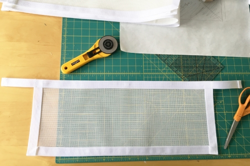 """I cut white vinyl mesh the length of the shelves and about 9 inches high. I stitched 1 """" white poly webbing around three sides onto the front and then finished the top edge with a longer piece of webbing."""